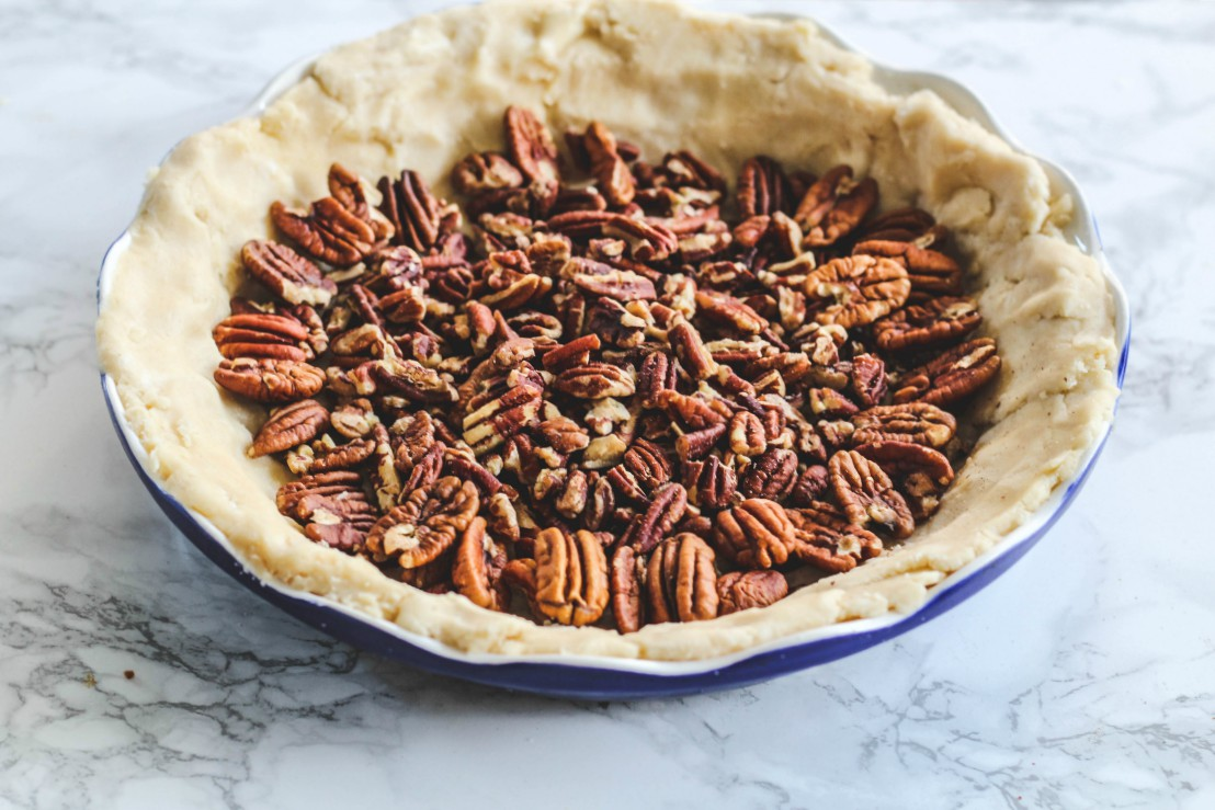 overhead image of nuts in a pie crust