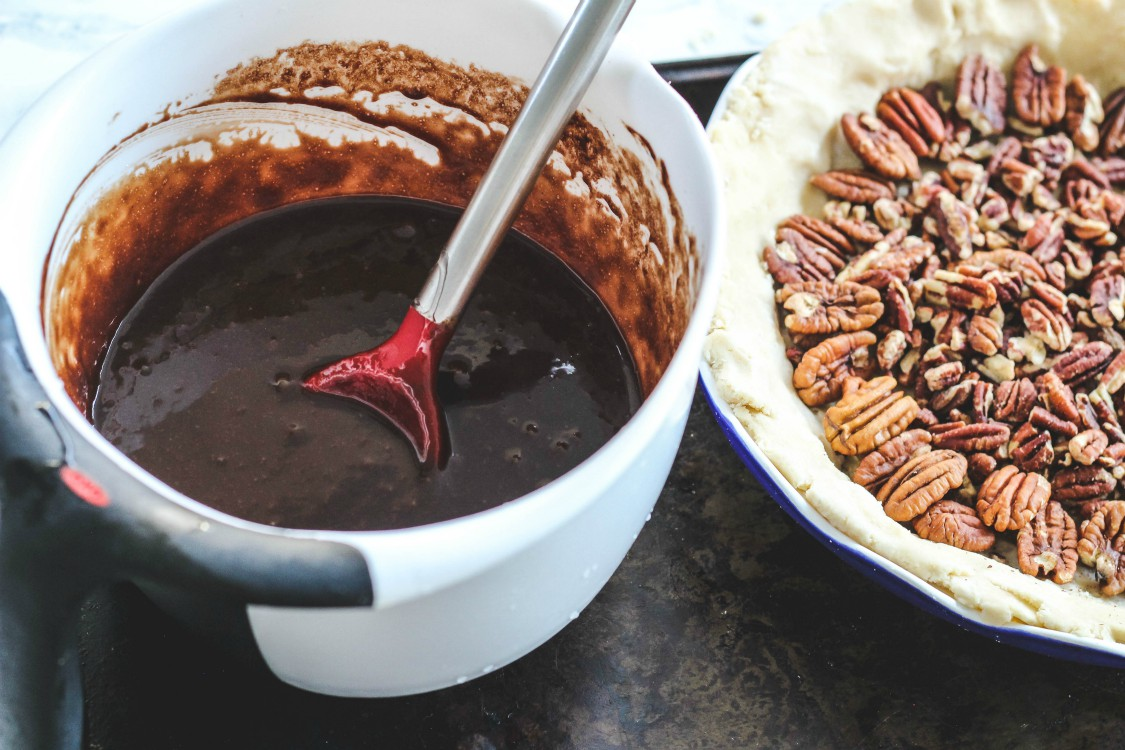overhead image of chocolate sauce in a white bowl next to pecans in a pie crust