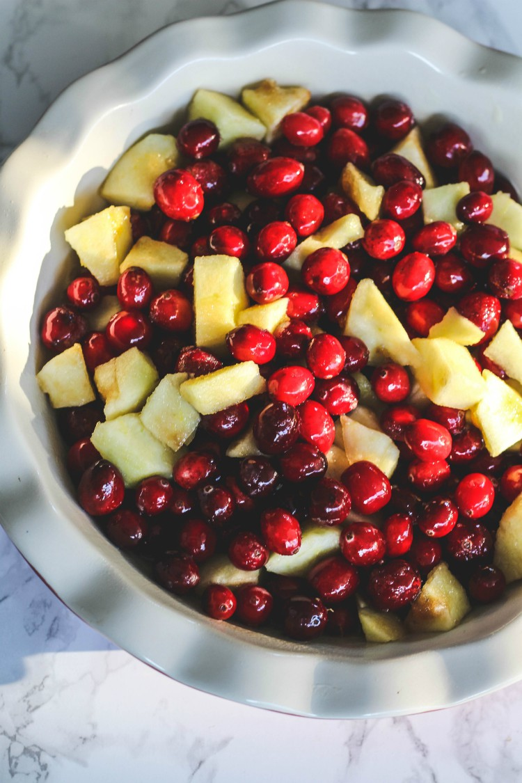 overhead image of apples and cranberries in white pie plate