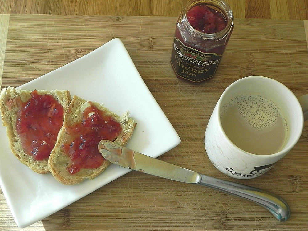overhead image of slices of bread with jam and cup of coffee