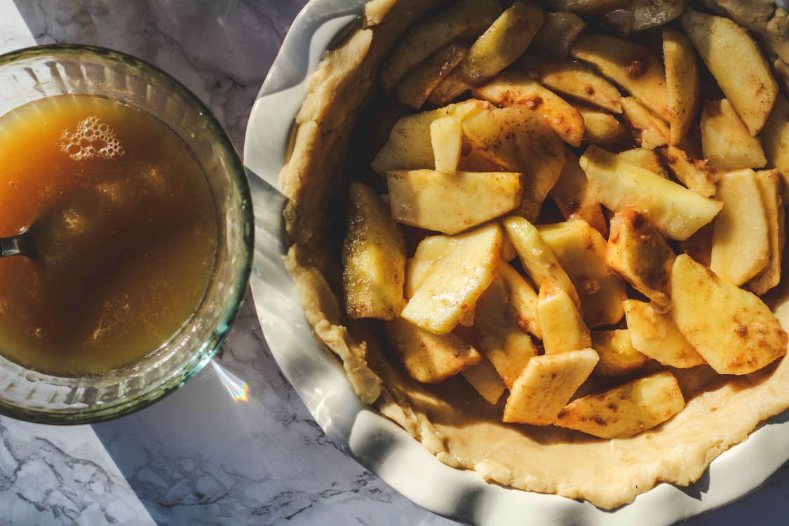 overhead image of caramel sauce and apples in a dough