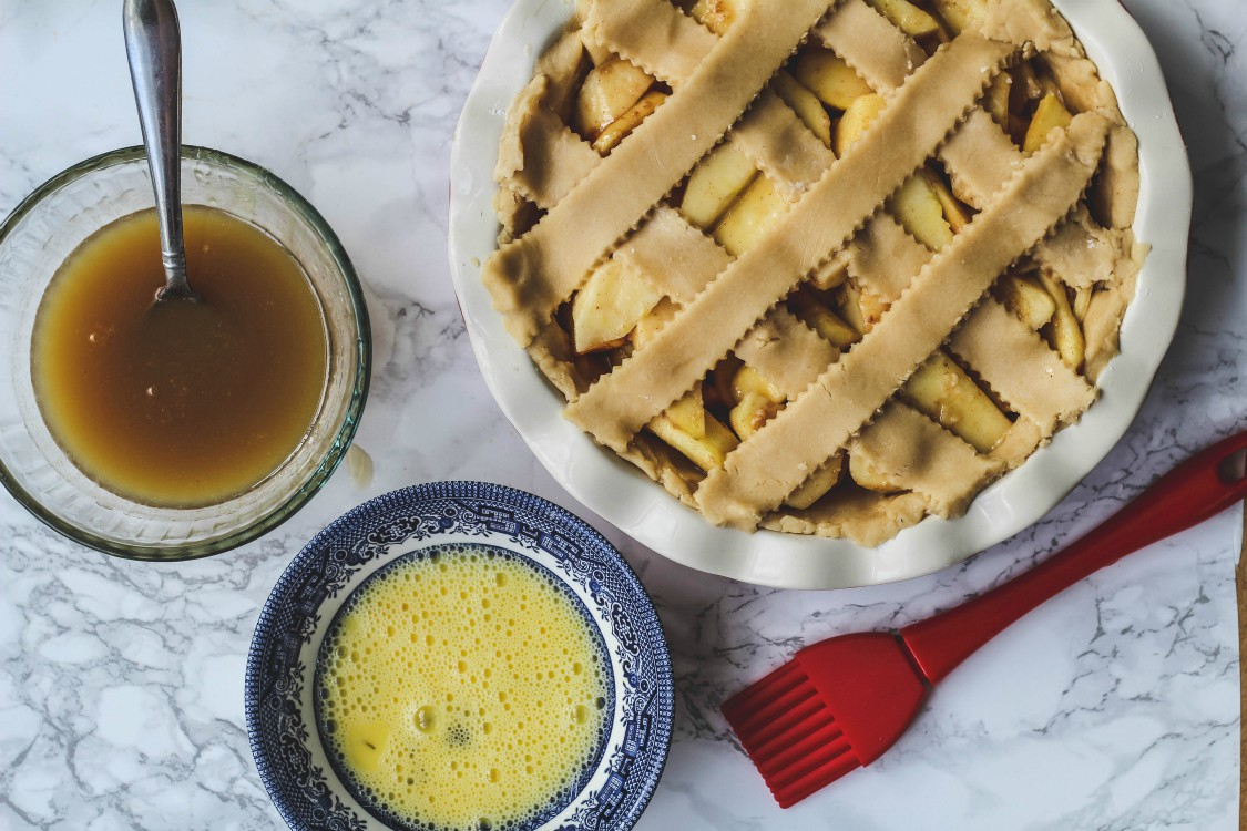 overhead image of caramel sauce, egg wash and lattice stripped pie