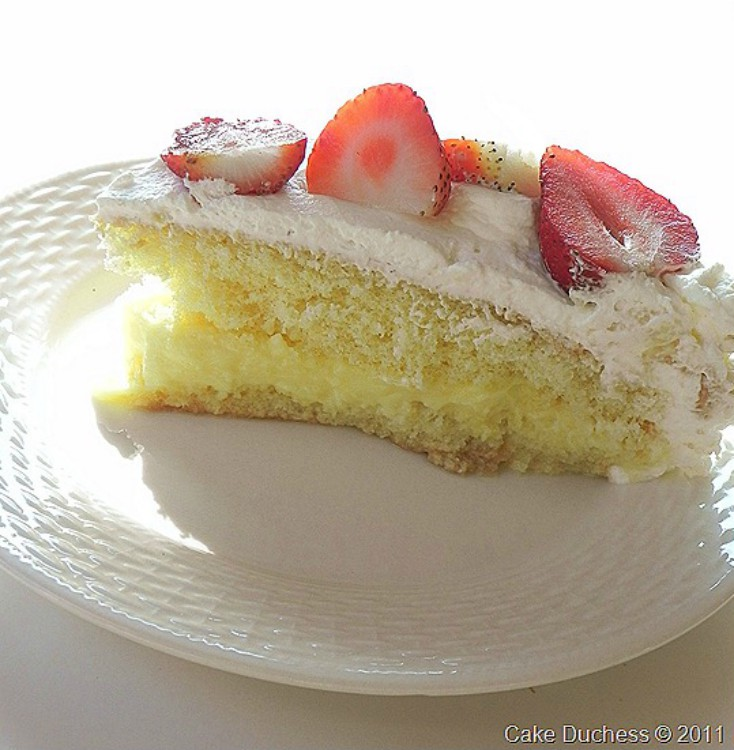 overhead image of slice of cake with whipped cream and berries on top