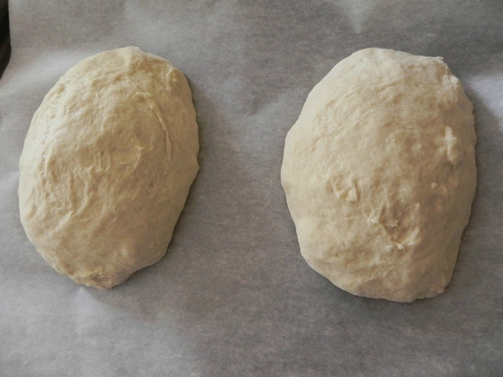 overhead image of bread loaves on parchment lined baking sheet