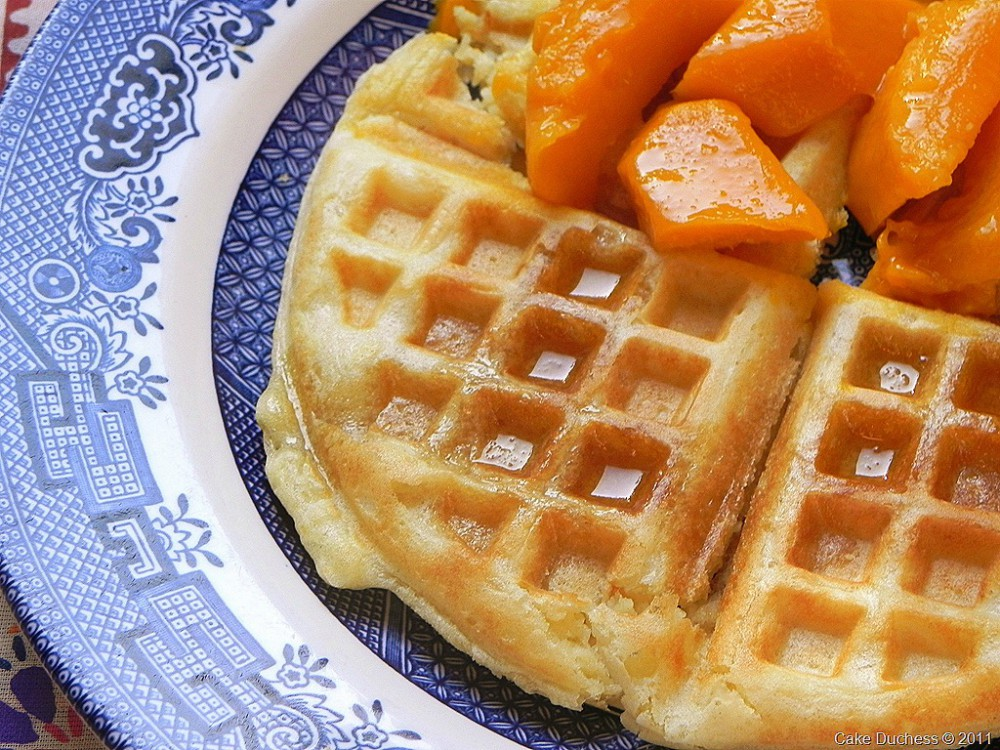 overhead image of waffles with orange fruit chunks on top