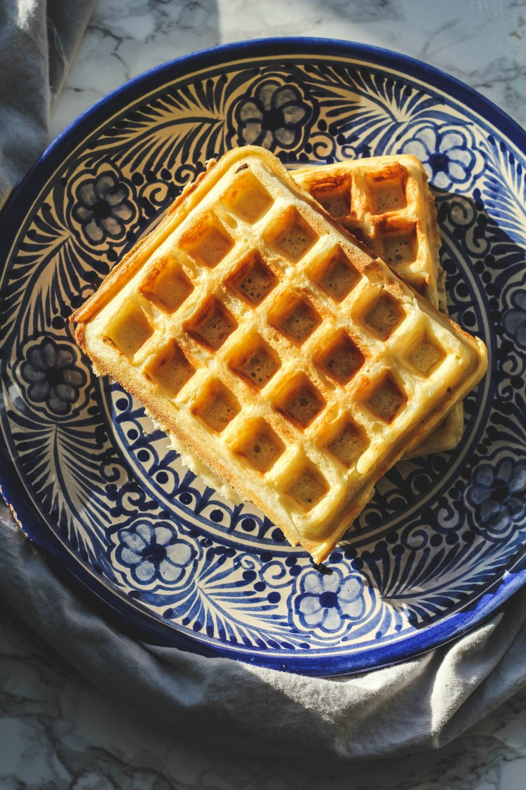 overhead image of waffles on a blue plate