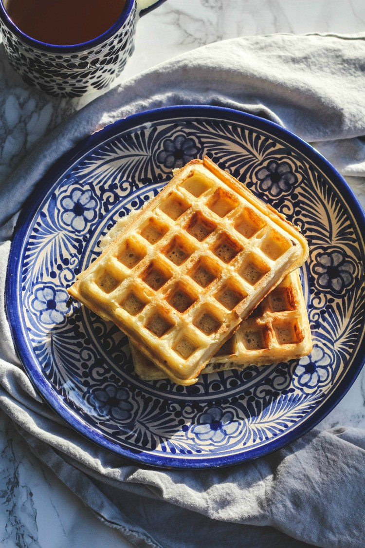 overhead image of raised waffles on a blue and white plate