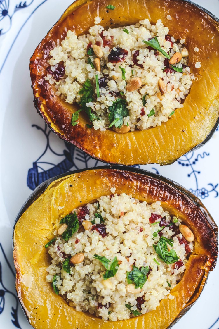 Overhead image of two halves of Stuffed Acorn Squash with Quinoa, Dried Cranberries and Pinoli.