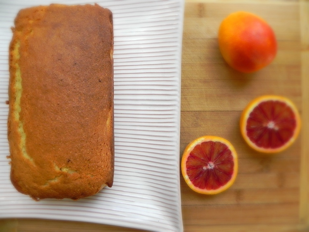 overhead image of loaf cake and sliced red orange