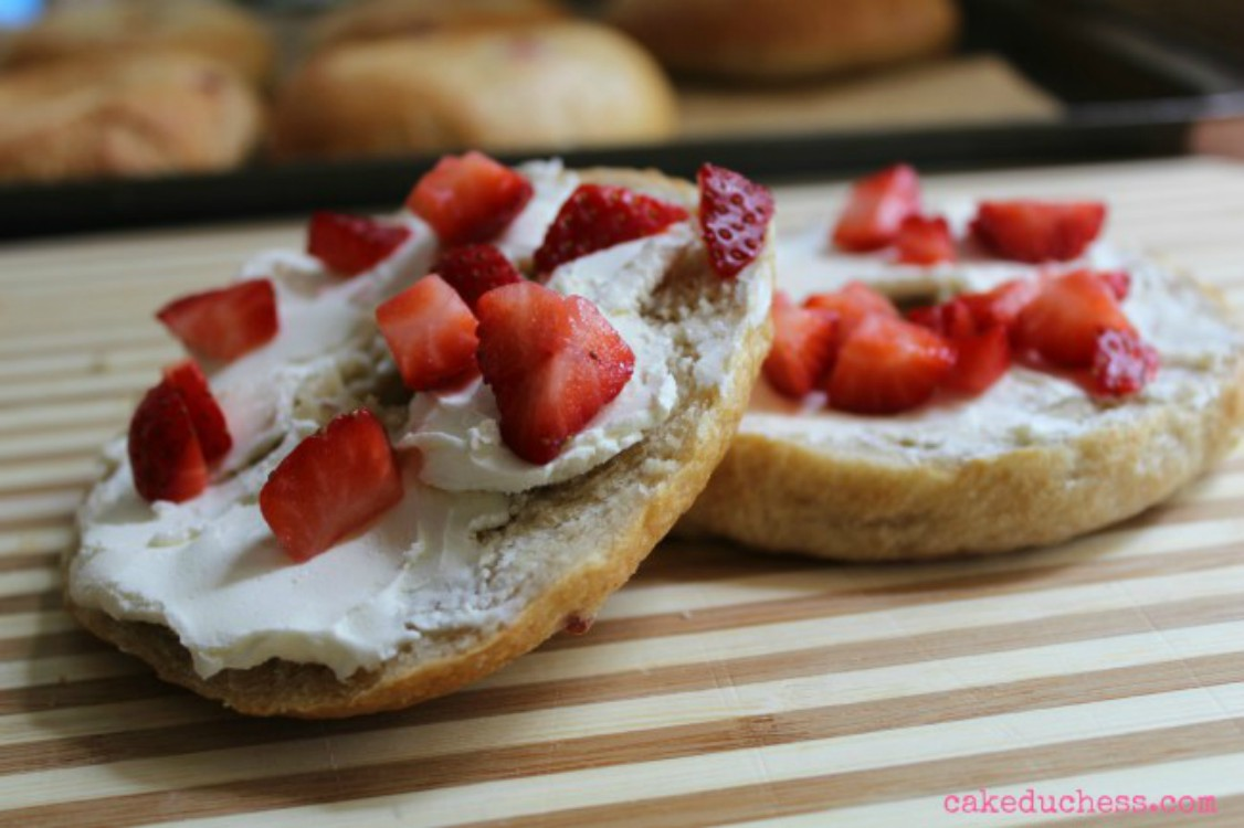 overhead image of bagel with cream cheese and strawberry chunks on wooden board