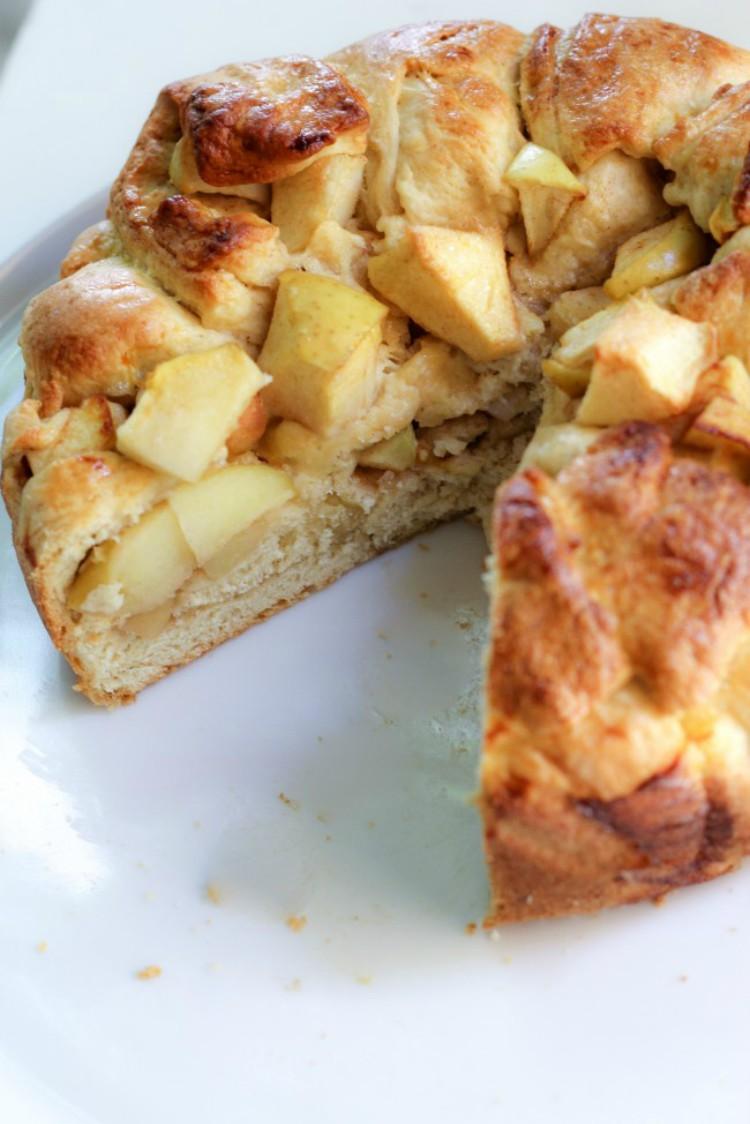 overhead image of apple harvest bread sliced on a white plate
