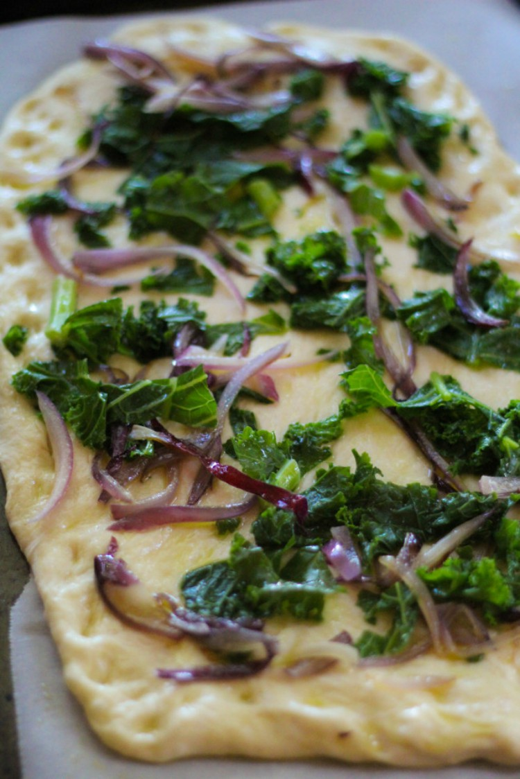 overhead image of kale and red onion pizza
