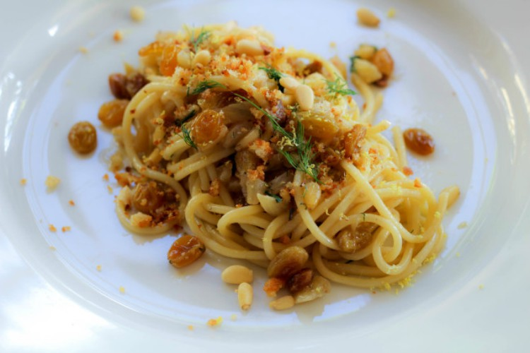 overhead image of spaghetti with nuts and raisins