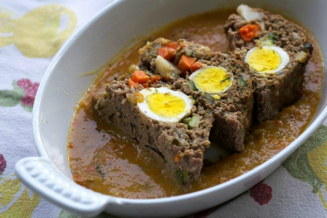 meatloaf with hardboiled eggs in a white baking dish with an orange sauce
