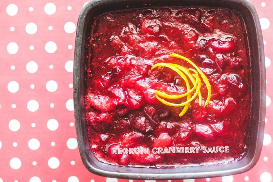 Italian cranberry sauce in a serving plate with orange rinds