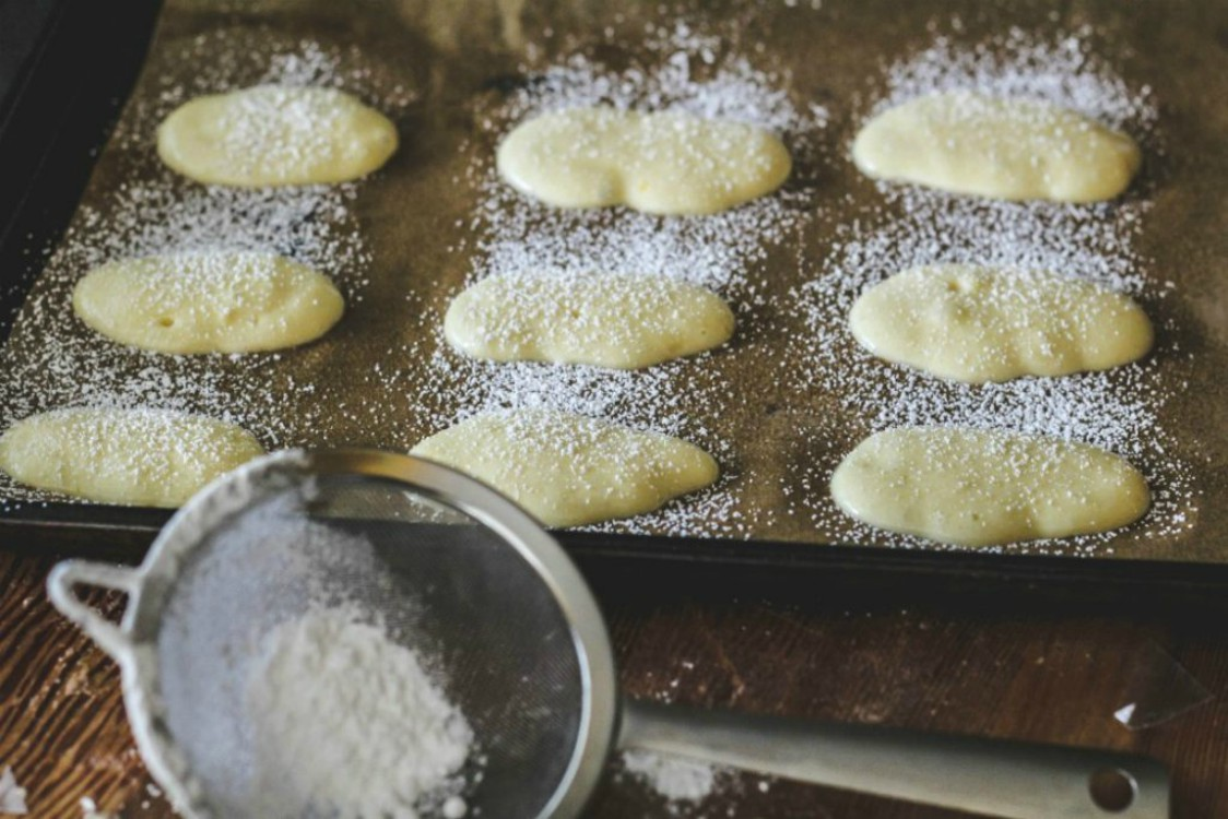 overhead image of ladyfinger cookies on baking tray