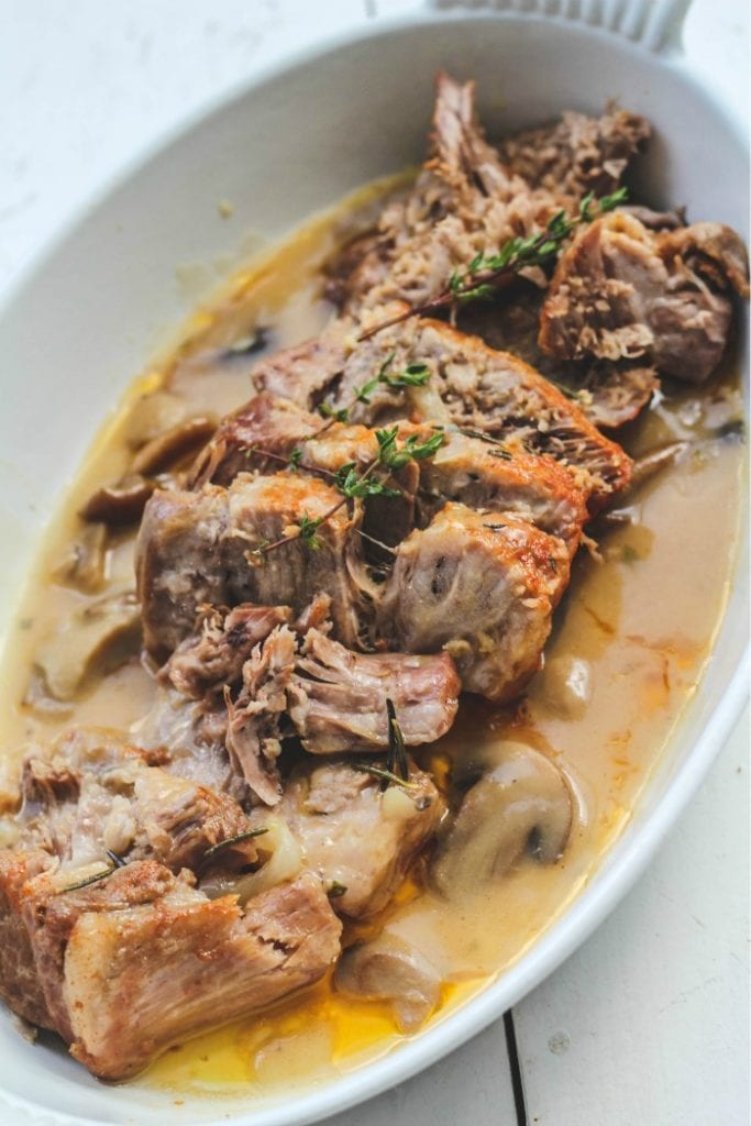 white serving dish filled with instant pot pork roast