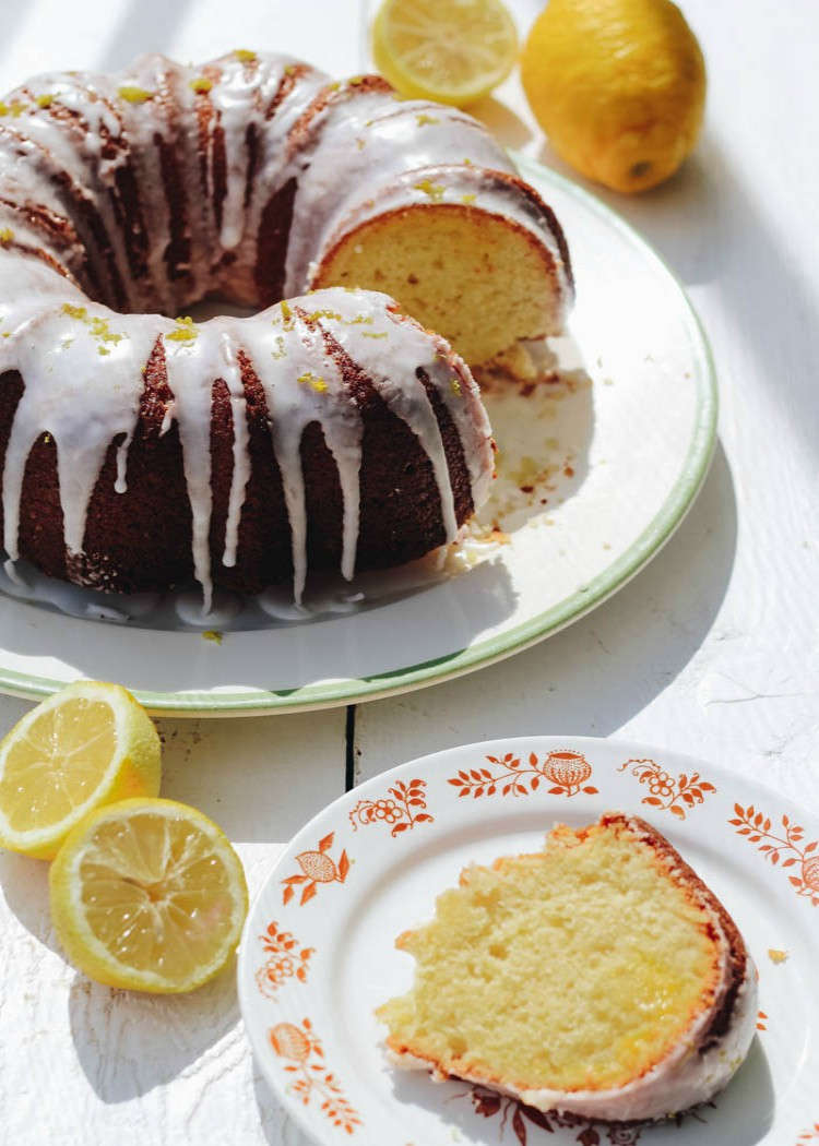 slice of lemon curd filled bundt cake on white plate next to entire bundt cake