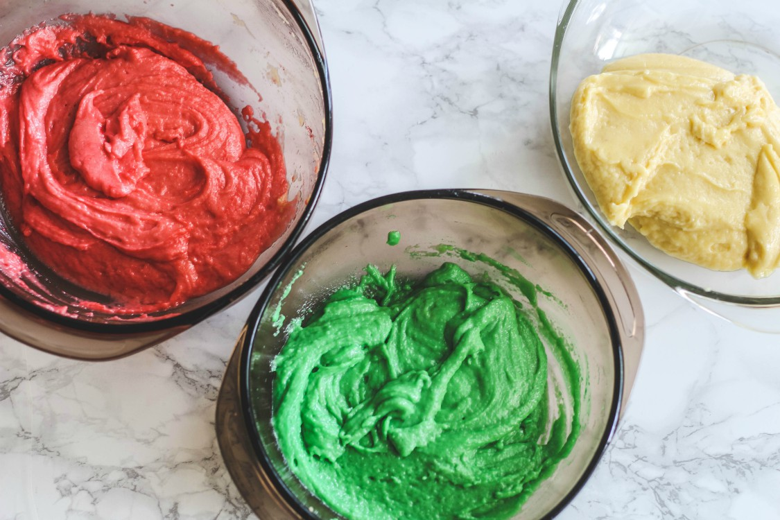 overhead imgae of colored dough in bowls