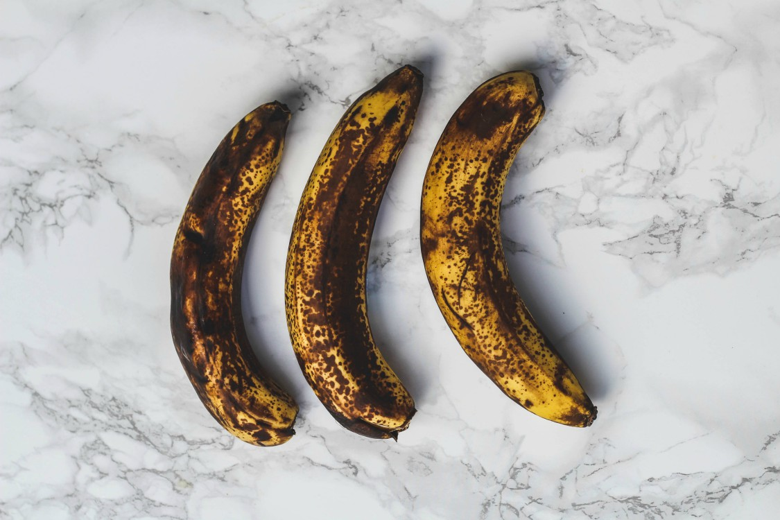 overhead image of ripe bananas on marble background