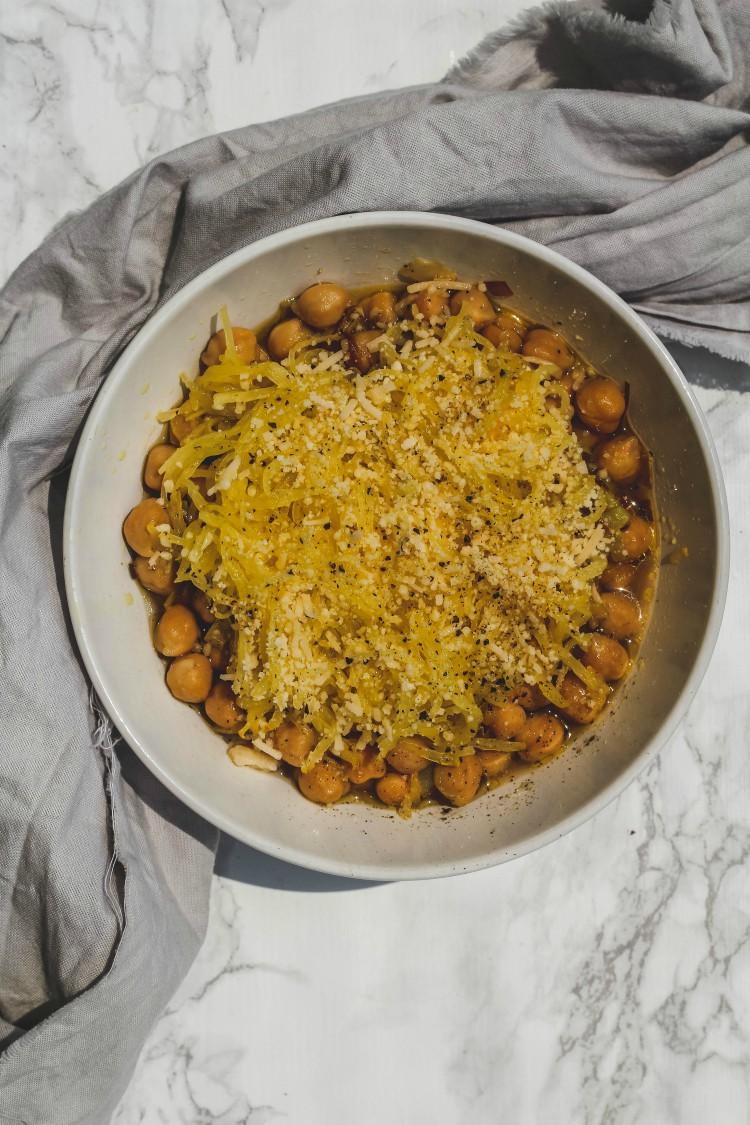 overhead image of cacio e pepe spaghetti squash with chickpeas in a white bowl