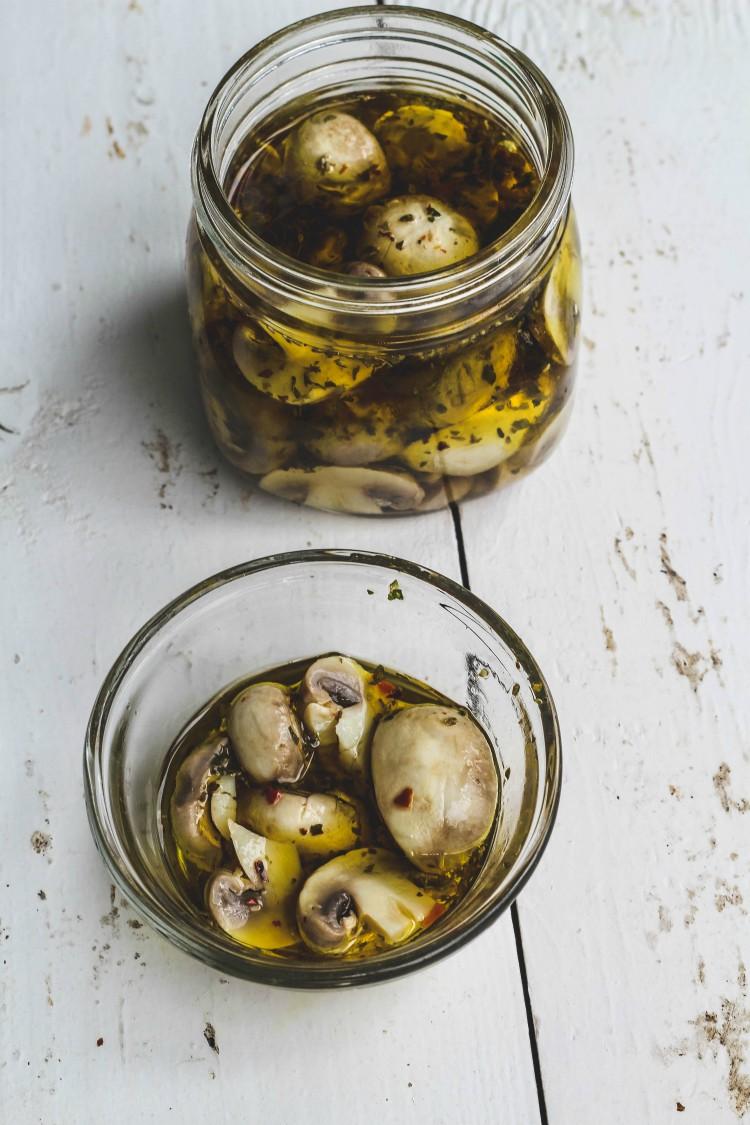 overhead image of marinated mushrooms in jars