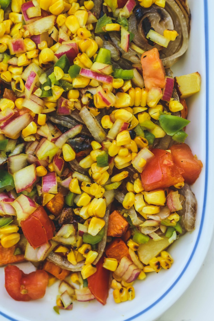 overhead image of roasted potatoes and sweet corn relish on a white plate