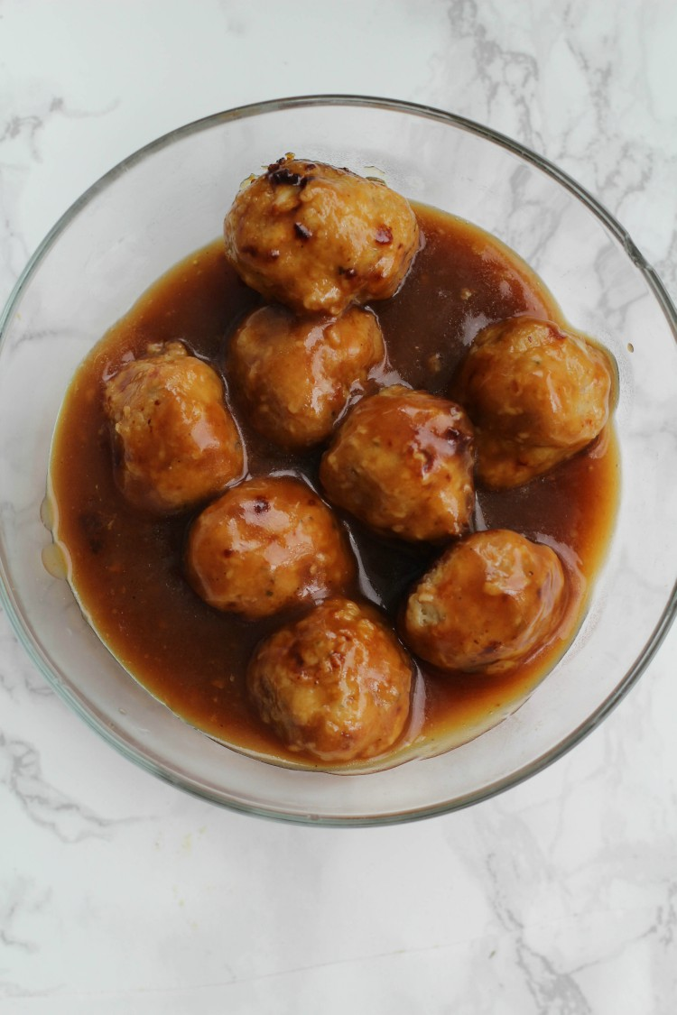 overhead image of orange chicken meatballs in a glass bowl