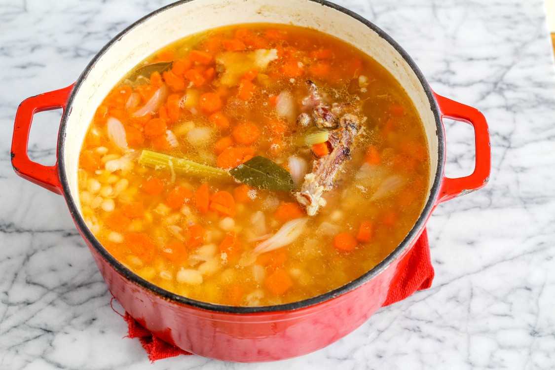 overhead image of Hungarian ham and bean soup in a red pot